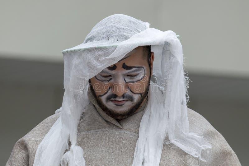 O ator masculino na roupa brilhante joga um meme em um teatro da rua imagem de stock royalty free