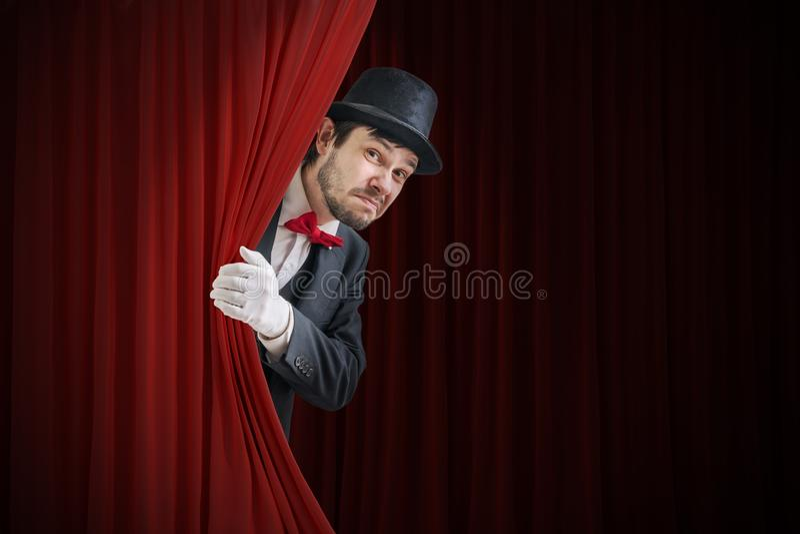 O ator ou o ilusionista nervoso estão escondendo atrás da cortina vermelha no teatro imagem de stock