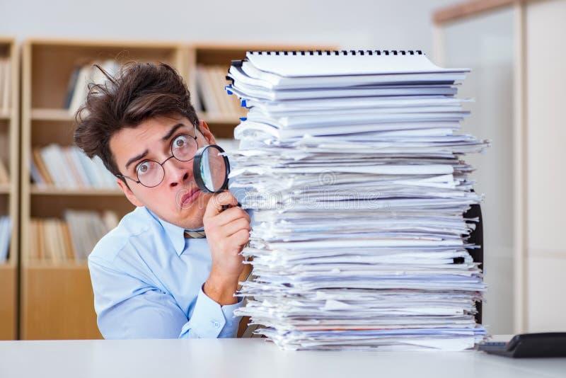 O auditor engraçado que verifica relatórios com a lupa fotos de stock