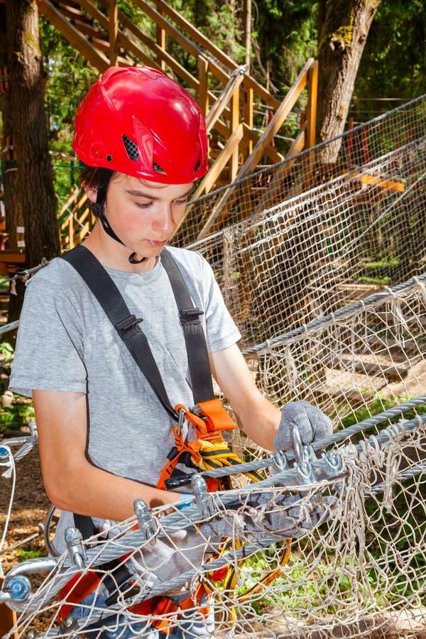O auto adolescente do ajuste do menino amarra o equipamento de segurança no cordas percorre em um parque da aventura da copa de á fotos de stock