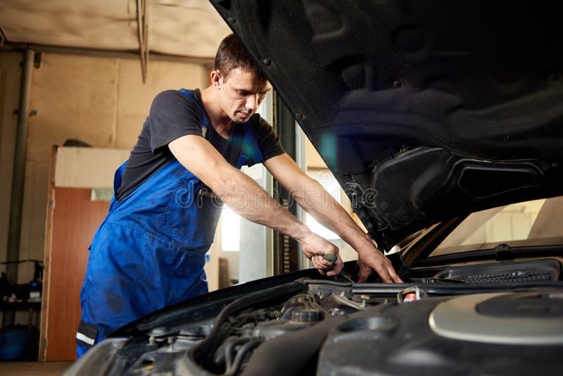 O auto mecânico no uniforme do trabalho sujo repara o carro na garagem imagens de stock royalty free