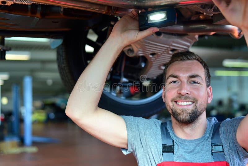 O auto mecânico repara o veículo em uma oficina imagens de stock royalty free