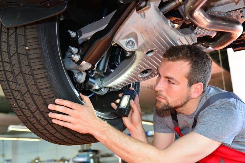 O auto mecânico repara o veículo em uma oficina fotos de stock royalty free