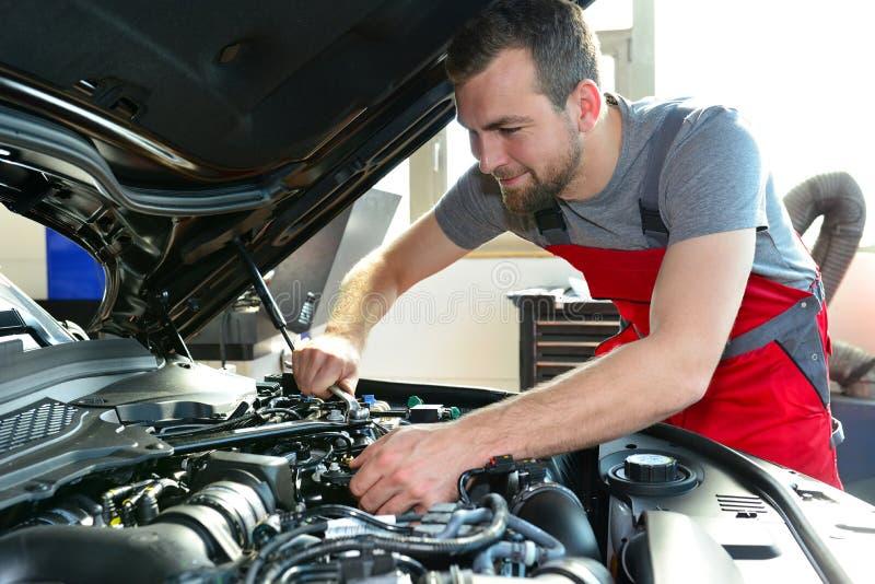 O auto mecânico repara o veículo em uma oficina fotografia de stock royalty free