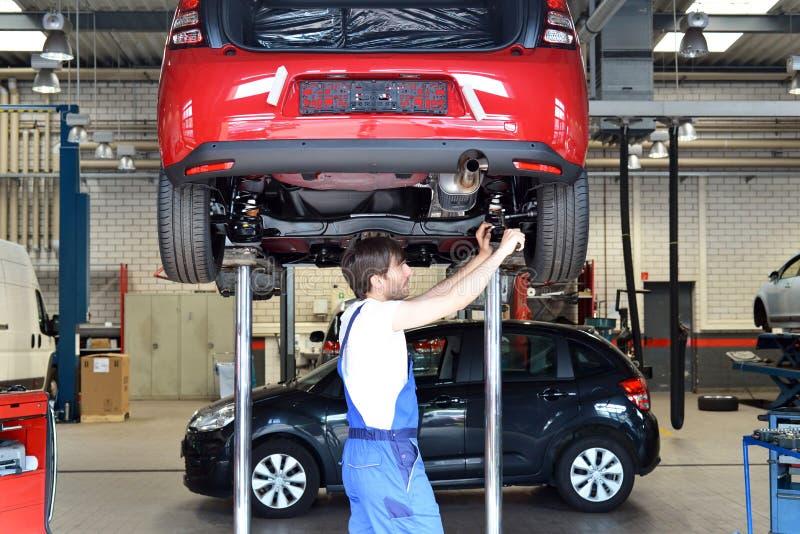 O auto mecânico repara o veículo em uma oficina fotos de stock