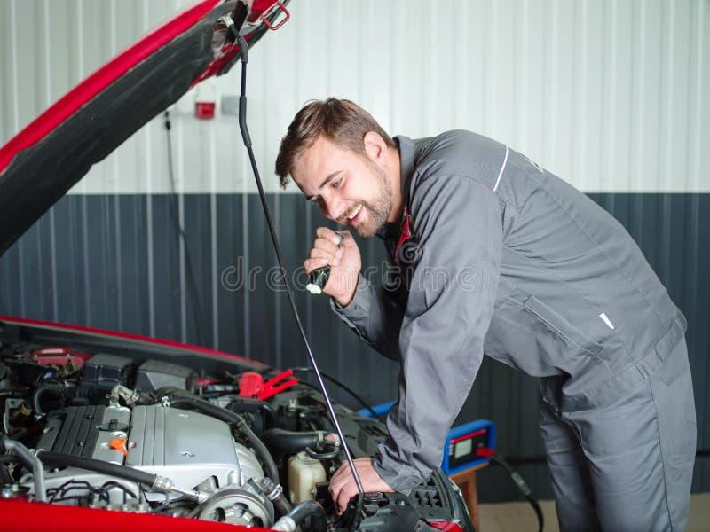 O auto mecânico verifica o carro sob a capa foto de stock