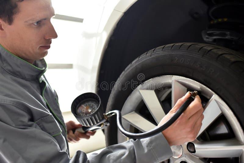 O auto mecânico verifica a pressão de ar de um pneu na garagem fotografia de stock