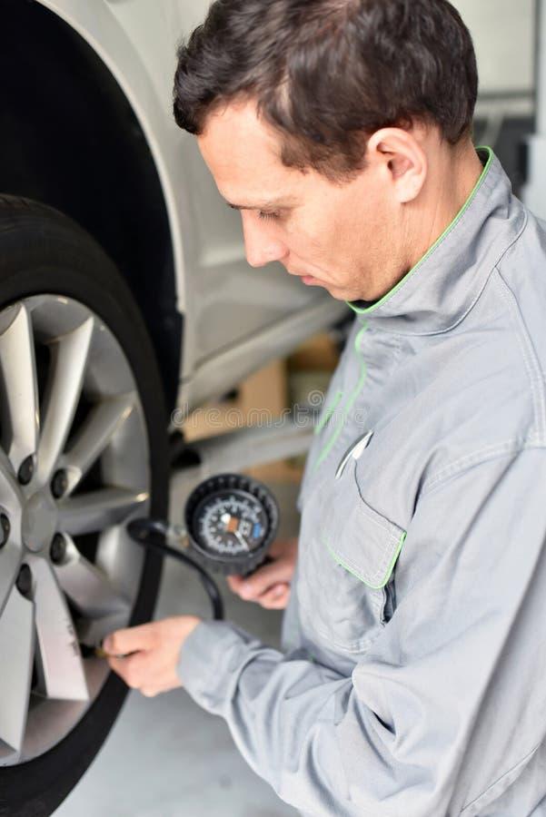 O auto mecânico verifica a pressão de ar de um pneu na garagem fotografia de stock royalty free