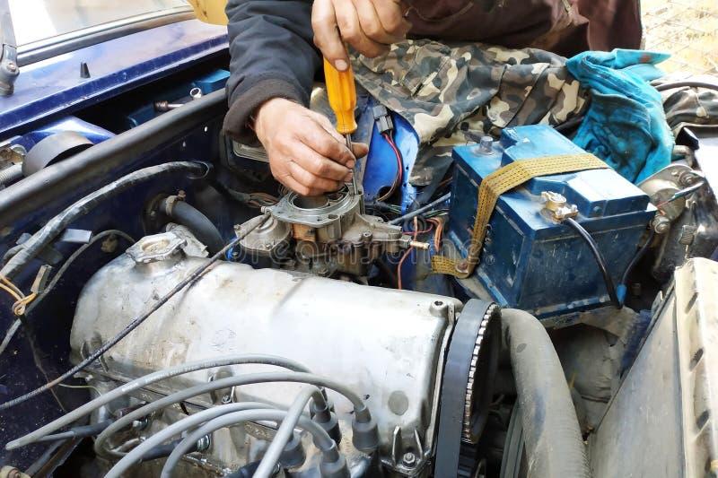 O auto serralheiro aperta as válvulas do na garagem imagem de stock royalty free