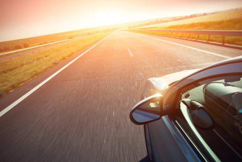 O automóvel move-se na velocidade rápida no nascer do sol imagens de stock royalty free