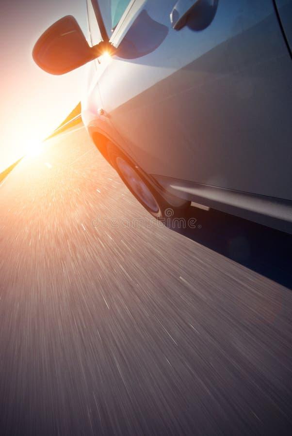 O automóvel move-se na velocidade rápida no nascer do sol imagens de stock