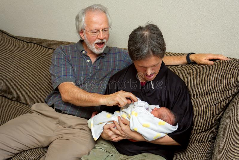 O avô do bebê recém-nascido ajuda seu cunhado com penas imagens de stock royalty free