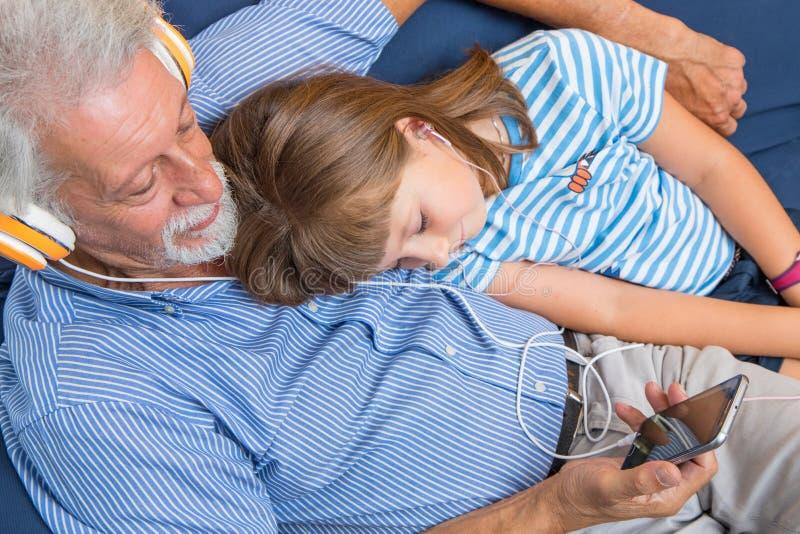 O avô e a filha escutam música com fones de ouvido imagem de stock