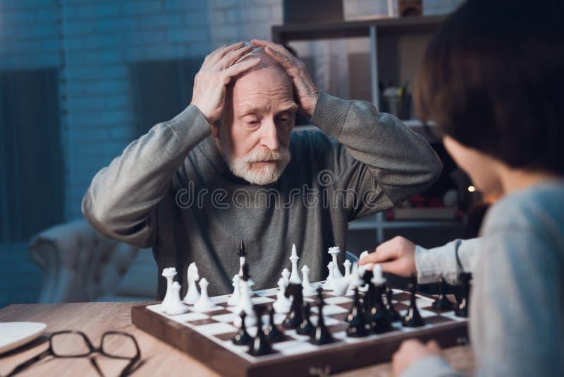 O avô e o neto estão jogando a xadrez junto na noite em casa fotos de stock royalty free