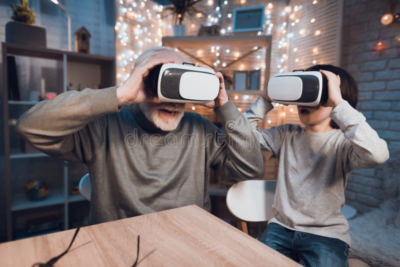 O avô e o neto estão usando a realidade virtual na noite em casa imagens de stock royalty free