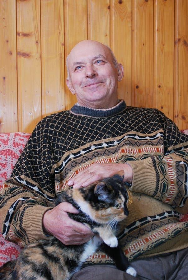 O avô senta-se em um sofá na dacha e passa-se o gato que senta-se nele em um regaço foto de stock royalty free