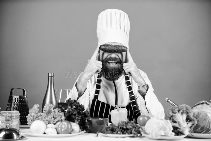 O avental do chap?u do cozinheiro do homem guarda legumes frescos Conceito da receita do vegetariano Restaurante do vegetariano M imagens de stock royalty free