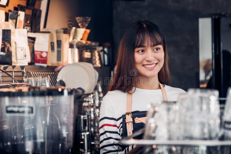 O avental fêmea asiático de brim do desgaste do barista na barra contrária com cara do sorriso, conceito do serviço do café, foto de stock