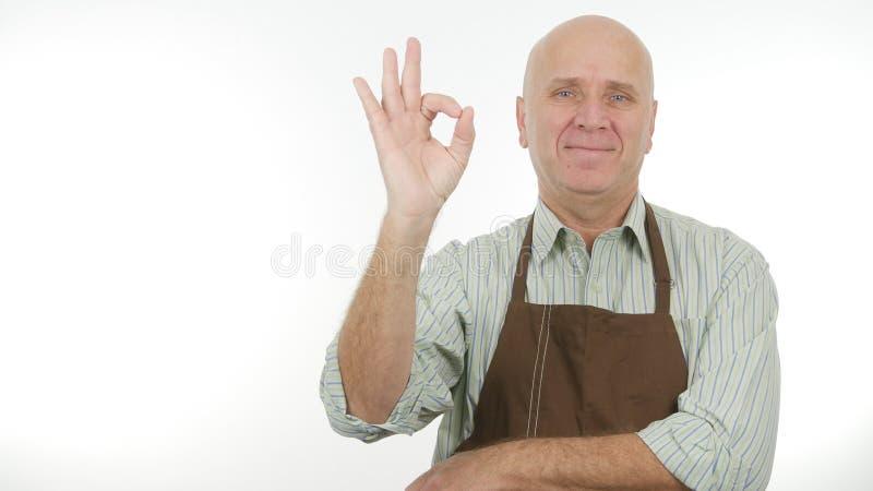 O avental vestindo da cozinha do homem feliz faz bons gestos da APROVAÇÃO do sinal do trabalho imagens de stock royalty free