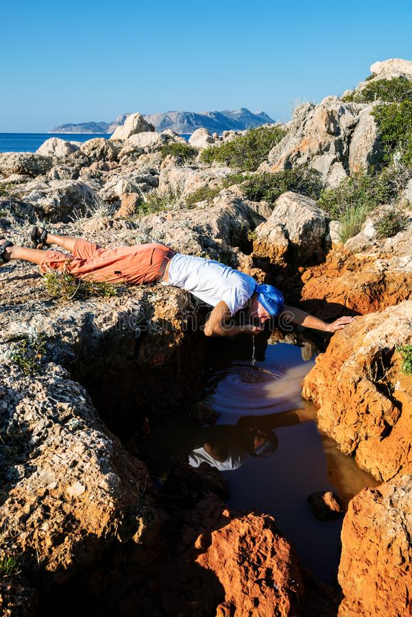 O aventureiro esgotado bebe a água de uma fenda em uma rocha fotografia de stock royalty free
