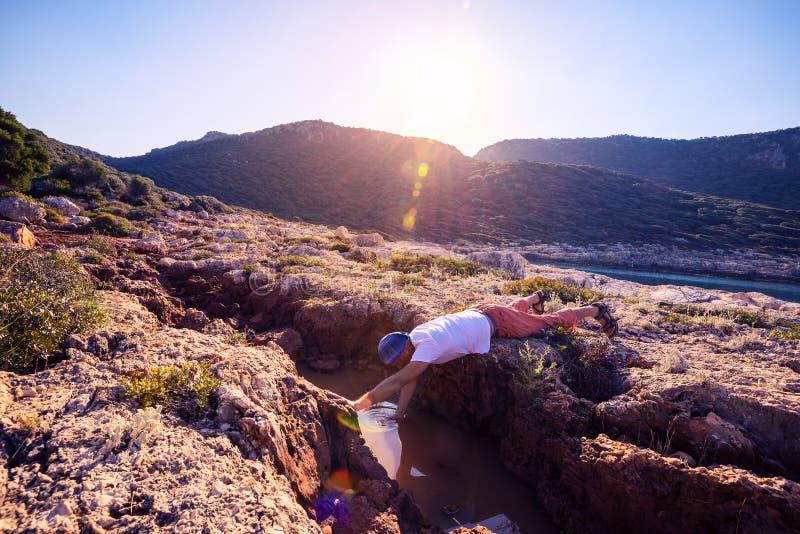 O aventureiro esgotado bebe a água de uma fenda em uma rocha fotografia de stock