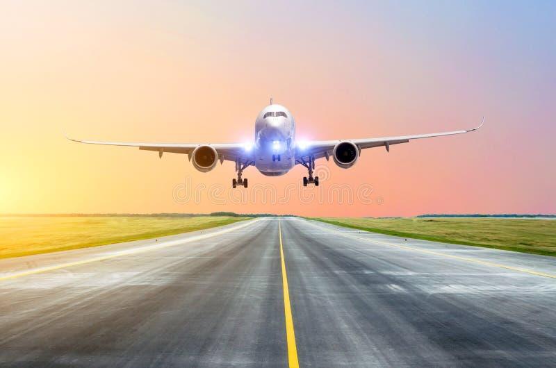 O avião com suas luzes sobre após decola a pista de decolagem no por do sol imagem de stock