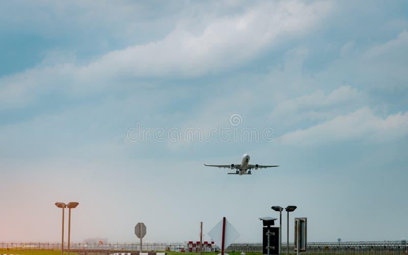 O avião comercial decola no aeroporto com o céu azul e as nuvens bonitos Deixando o voo Comece no exterior a viagem Tempo de féri foto de stock