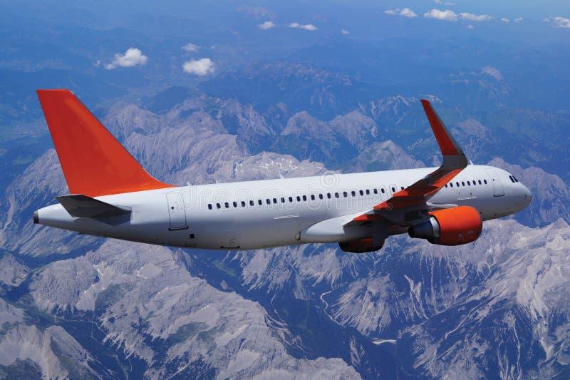 O avião comercial voa sobre as montanhas, a silhueta inteira o fotografia de stock