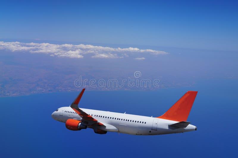 O avião comercial voa sobre o mar, toda a silhueta imagem de stock