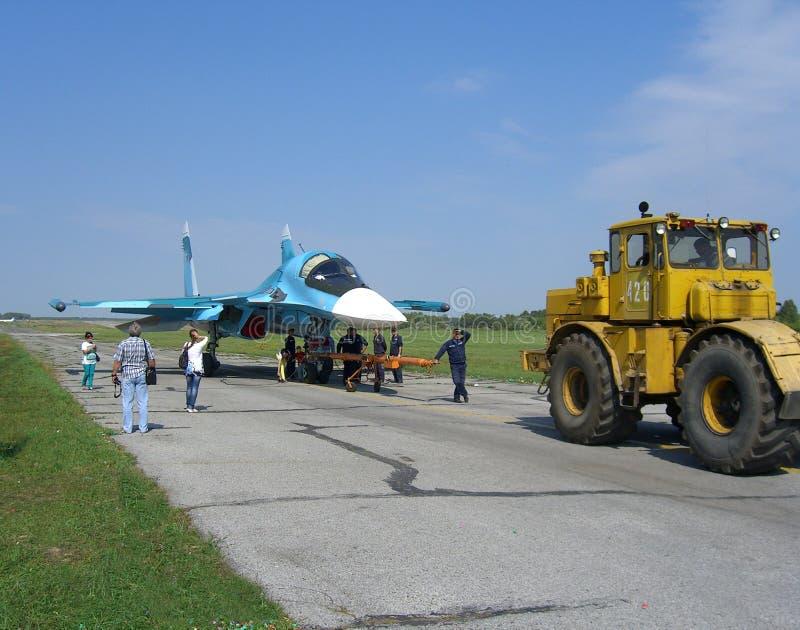 O avião de combate militar do jato do russo poderoso na pista de decolagem do trator SU-34 leva o motor foto de stock royalty free