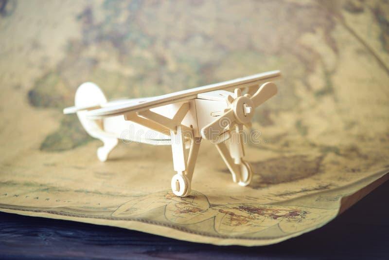 O avião de madeira do brinquedo voa no fundo do mapa do mundo no estilo retro imagens de stock
