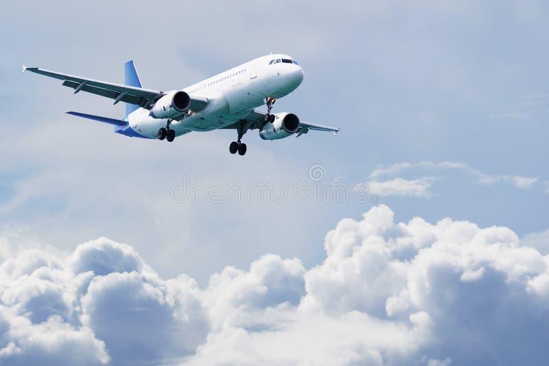 O avião de passageiros do passageiro voa acima das nuvens foto de stock