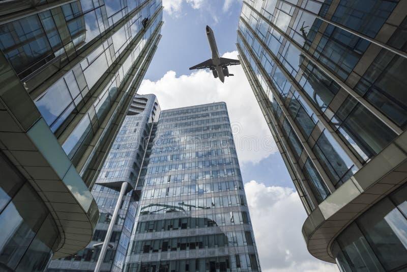 O avião de passageiros voou acima da construção de vidro moderna fotos de stock