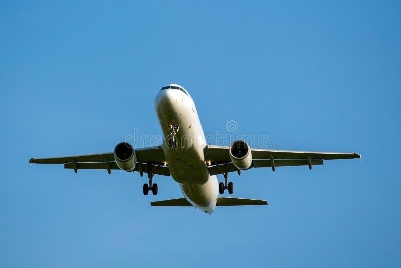 O avião de passagem faz uma aterrissagem, o fundo é um céu azul, vista dianteira imagens de stock