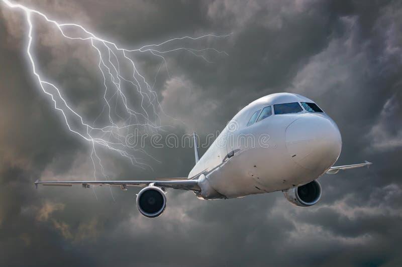 O avião está voando na tempestade Nuvens e relâmpago escuros no fundo foto de stock royalty free