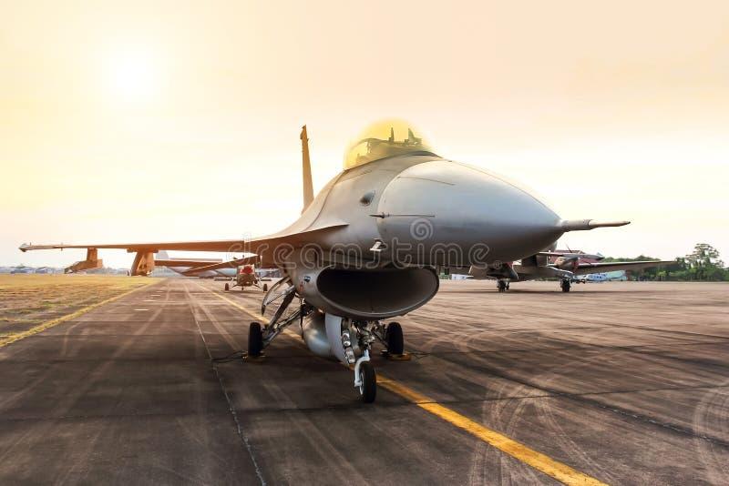 O avião militar do avião de combate do falcão estacionou na pista de decolagem no por do sol fotografia de stock