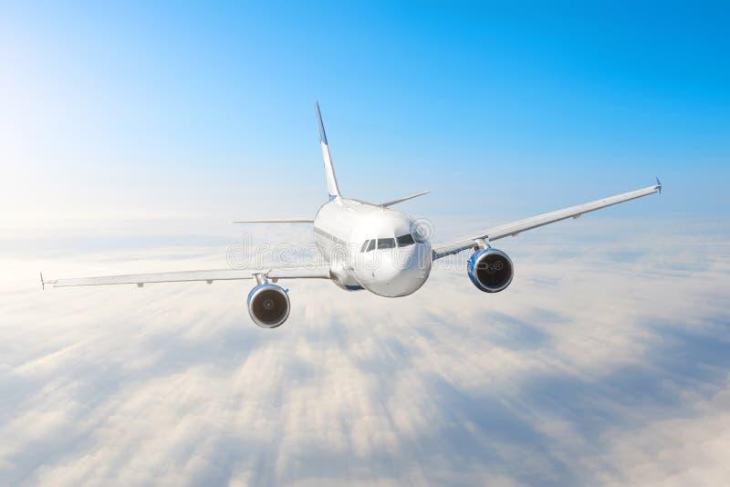 O avião no céu acima das nuvens migra o borrão de movimento da velocidade da altura do sol da viagem Aviões comerciais do passage imagens de stock