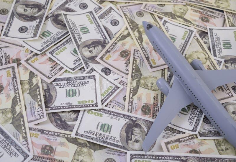 O avião no dinheiro, os aumentos do custo da linha aérea viaja imagens de stock