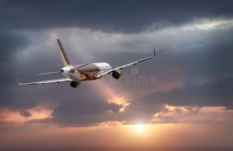 O avião voa para o céu tempestuoso fotos de stock royalty free