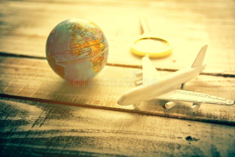 O avi?o e o globo pequenos e ampliam vidros no fundo de madeira da textura da tabela Curso e férias do mapa do mundo em todo o mu fotos de stock