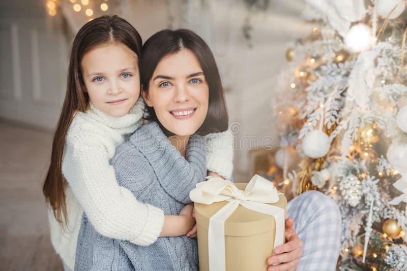 O azul adorável eyed a criança que pequena os huggs com grande amam sua mãe que guarda a caixa de presente envolvida, árvore próx fotografia de stock