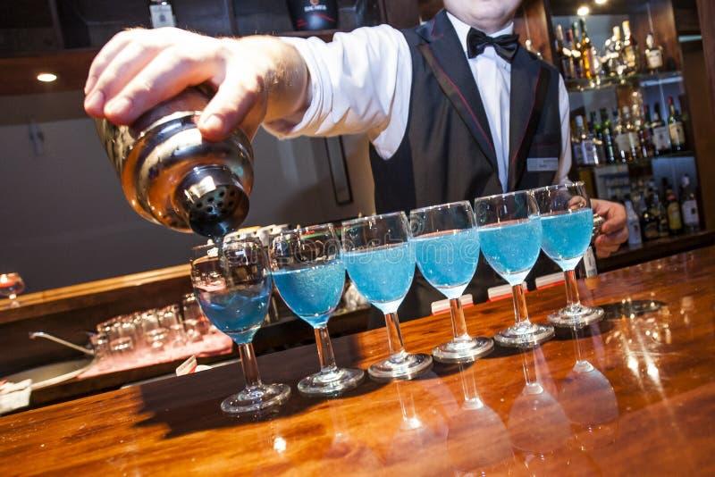 O azul de derramamento do empregado de bar colorido bebe aos vidros na barra co imagens de stock royalty free