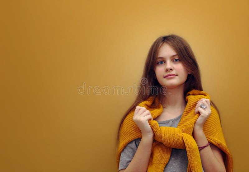 O azul eyed a menina tímida de cabelo marrom com cabelo de fluxo em uma camiseta em um fundo foto de stock