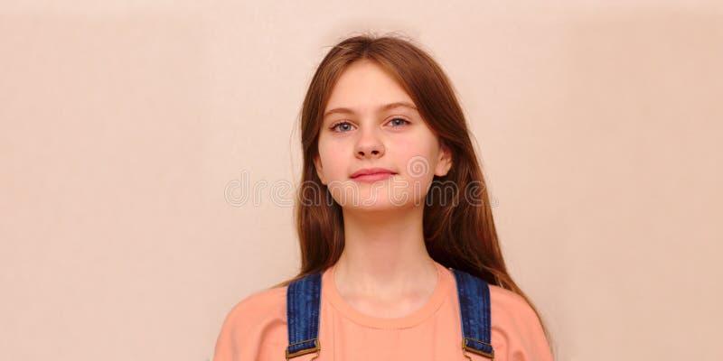 o azul eyed a menina tímida de cabelo marrom em macacões da sarja de Nimes Tiro modelo do estúdio imagem de stock royalty free