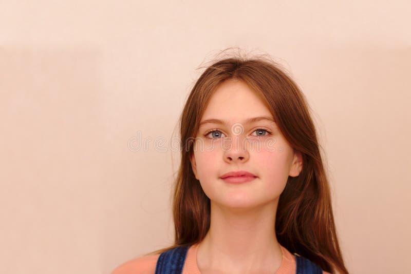 o azul eyed a menina tímida de cabelo marrom em macacões da sarja de Nimes Tiro modelo do estúdio foto de stock