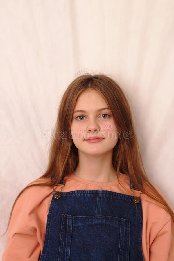 o azul eyed a menina tímida de cabelo marrom em macacões da sarja de Nimes Tiro modelo do estúdio foto de stock royalty free