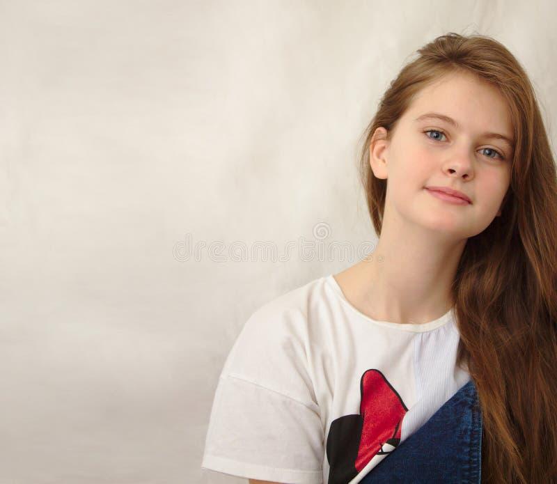 o azul eyed a menina tímida de cabelo marrom em macacões da sarja de Nimes Tiro modelo do estúdio imagens de stock royalty free