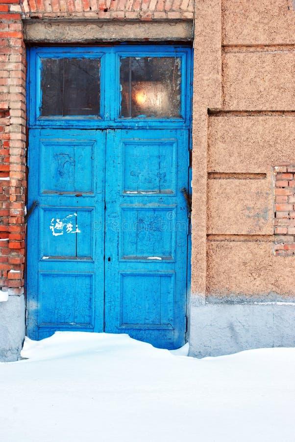 O azul fechado pintou a porta com a janela na parte superior, parede de pedras velha dos tijolos vermelhos, fundo do grunge imagens de stock