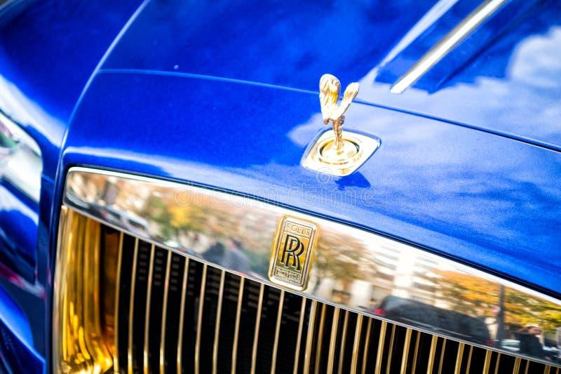 O azul luxuoso do fantasma de rolls royce rolls royce do supercarro e a cor do ouro estacionaram na rua em Paris rolls royce roll imagens de stock