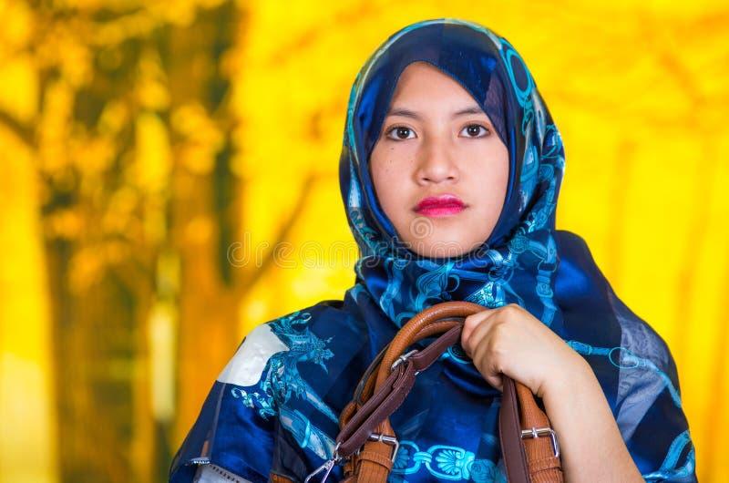O azul vestindo da mulher muçulmana nova bonita coloriu o hijab, olhando fixamente na câmera, guardando a bolsa de couro, florest fotografia de stock